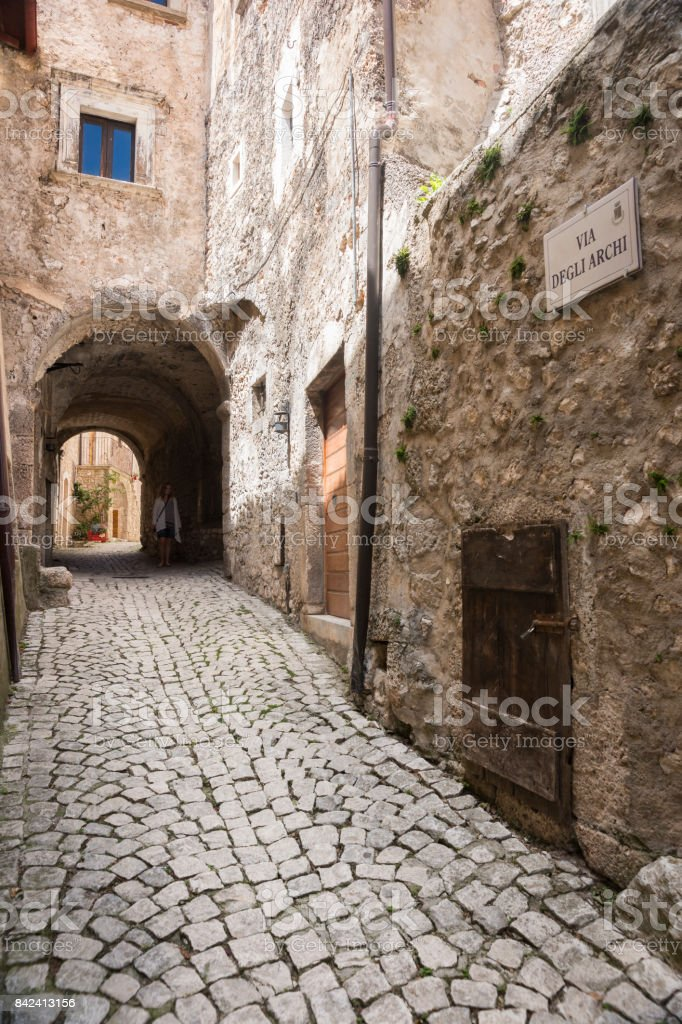 Street scene of ancient stone buildings, arched entrances, narrow lanes, wooden doors and cobblestone streets in the tiny medieval fortified village of Santo Stefano di Sessanio; Gran Sasso National Park; L'Aquila Province, Abruzzo; Italy; Europe stock photo