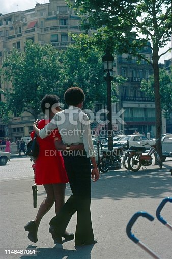 Champs Elysee, Paris, Il de France, 1973. Street scene with a passing couple on the boulevard Champs Elysee in Paris.