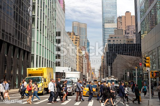 Street scene in Midtown Manhattan with pedestrians crossing Park Avenue at the intersection,  cars standing at traffic light.