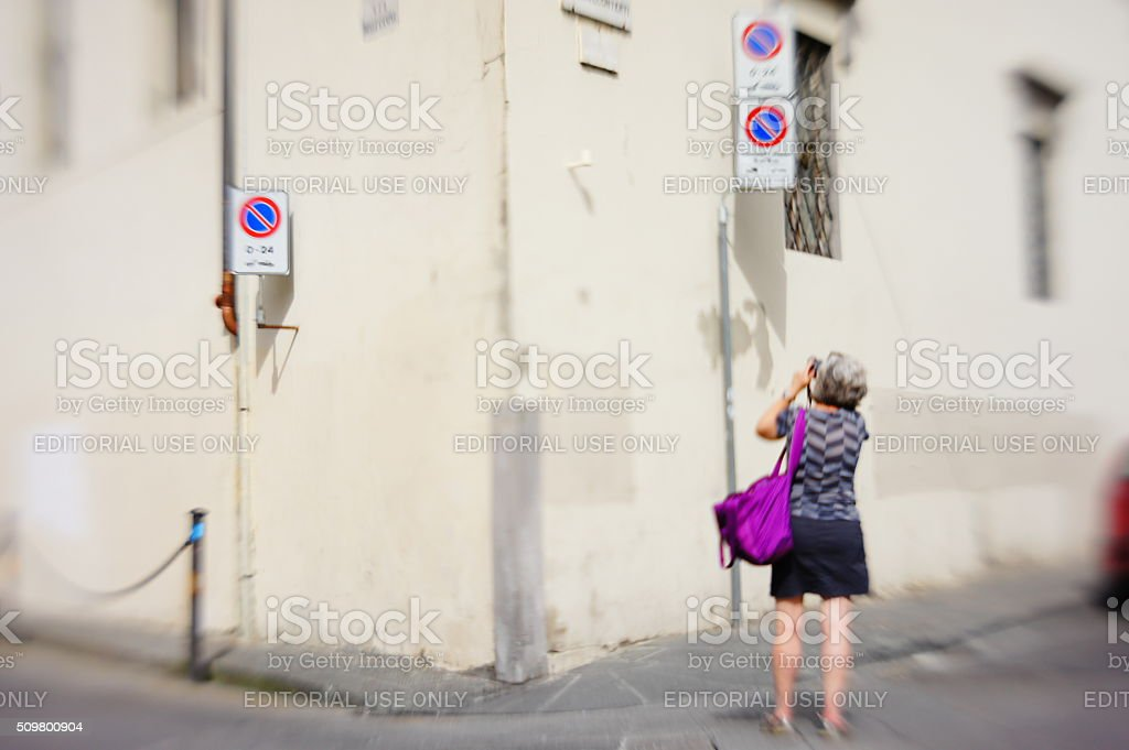 Street scene: Woman photographs a blank building with road signs stock photo