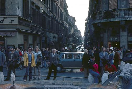 Rome, Lazio, Italy, 1974. Street scene with tourists and locals in the Piazza di Spagna (Bernini fountain). Also: road traffic, buildings and shops.