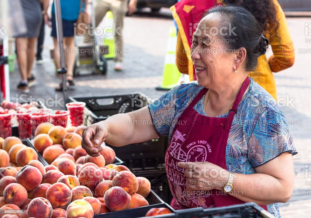 Street seller selling peach at Farmers Market, Seattle. stock photo