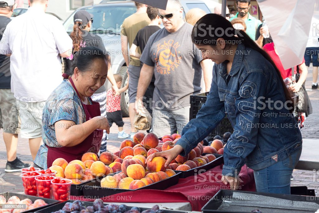 Street seller selling peachs at Farmers Market, Seattle. stock photo
