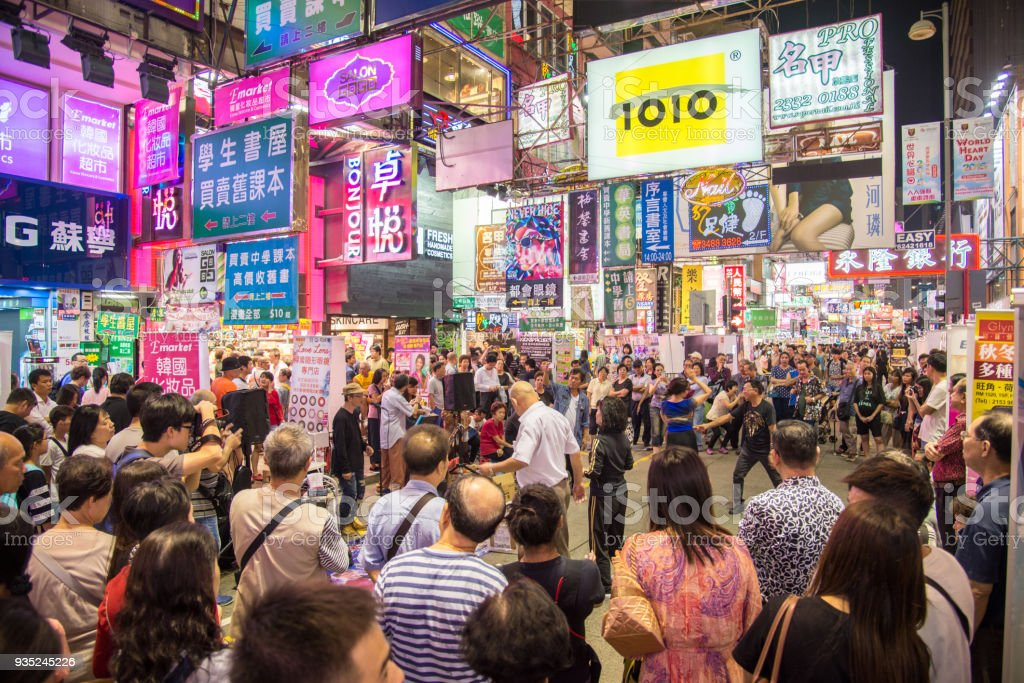 Street show on Mongkok area. Mong Kok is characterized by a mixof old and new multi-story buildings HONG KONG - October 10, 2015: Street show on Mongkok area. Mong Kok is characterized by a mixof old and new multi-story buildings, with shops and restaurants at street level and commercial or residential units above. Adult Stock Photo
