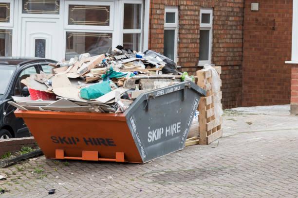 street side skip filled with rubish - obsoleto foto e immagini stock