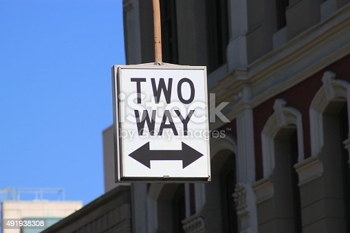 Street sign for Two Way traffic symbolized by a white sign with black letters stating TWO WAY and a thick black arrow pointing in both directions