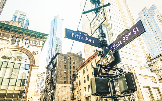 istock Street sign of Fifth Ave and West 33rd St in New York City - Urban concept and road direction in Manhattan downtown - American world famous capital destination on azure desaturated afternoon filter 1064344992