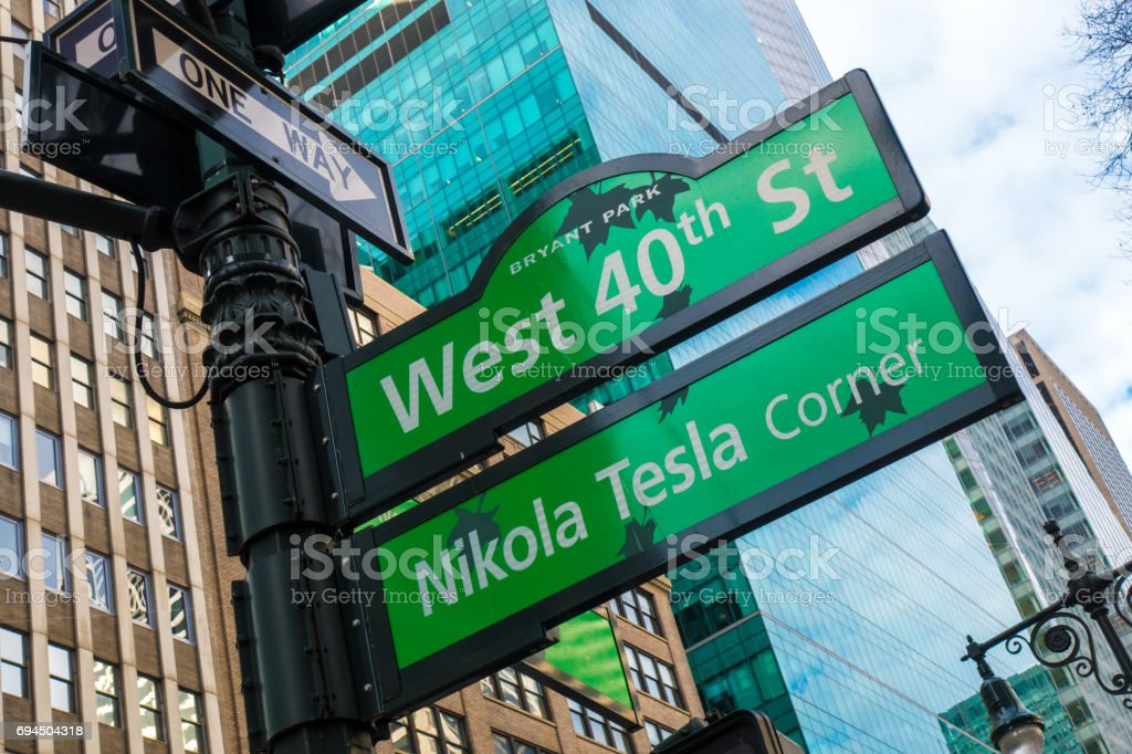 Street sign of Nikola Tesla corner and West 40th St with skylines in background.- New York, USA stock photo