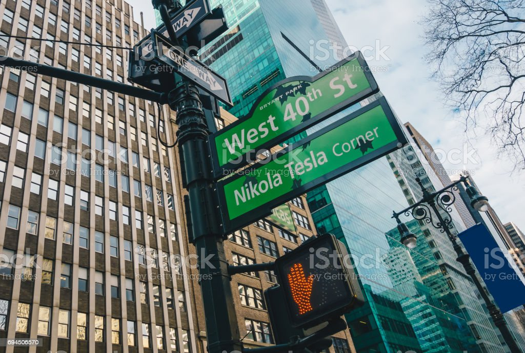 Street Sign Of Nikola Tesla Corner And West 40th St With Skylines In