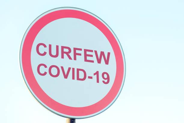 straatnaambord met avondklok, virus covid-19. - avondklok stockfoto's en -beelden