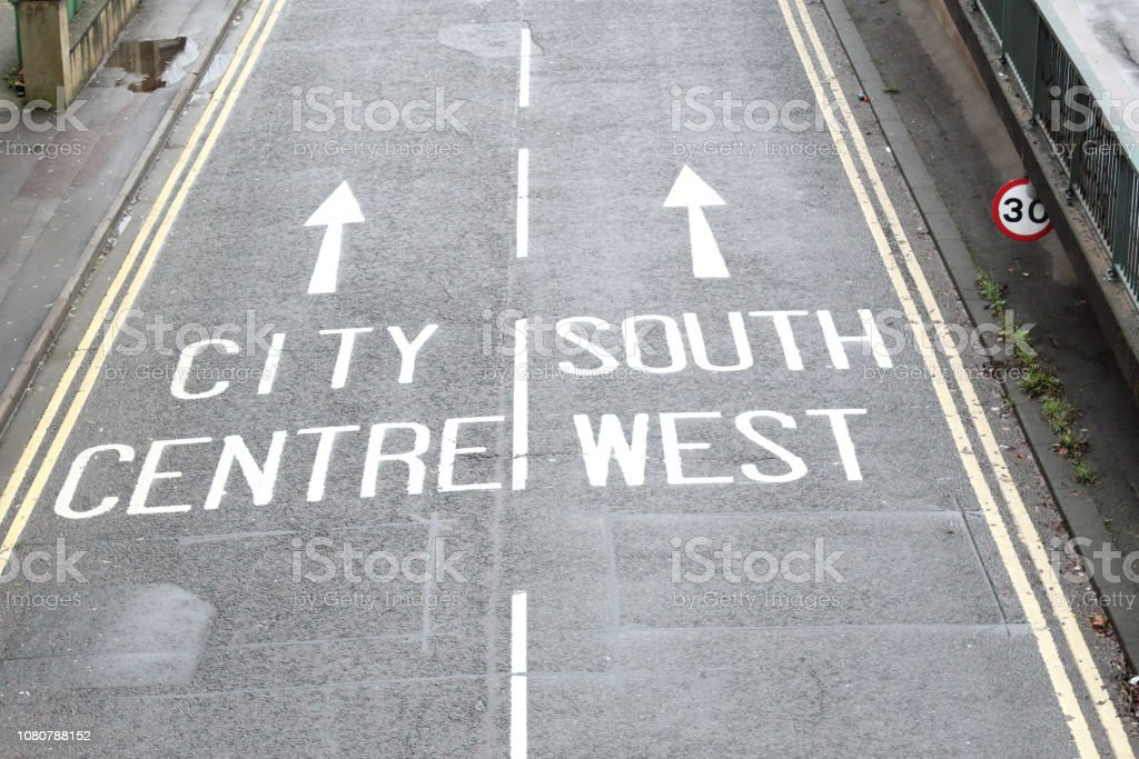 Street signs painted on an asphalt paved street showing City Centre...