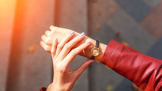 Street style fashion details. close up, young fashion blogger wearing a jacket and a analog wrist watch. stylish woman checking the time on her watch. autumn fall season