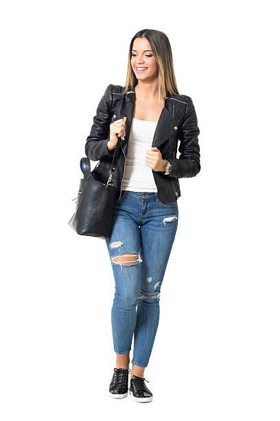 street style fashion girl with handbag smiling and looking down - handtasche jeans stock-fotos und bilder