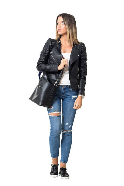 street style fashion model carrying bag walking and looking away - handtasche jeans stock-fotos und bilder