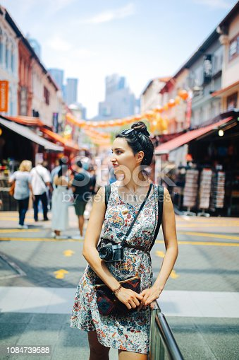 Vintage toned street style image of a young brunette woman. She is enjoying the walk and exploring the city, wearing a casual but fashionable dress on the streets of Singapore.