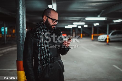 Street style man using smart phone in the parking lot