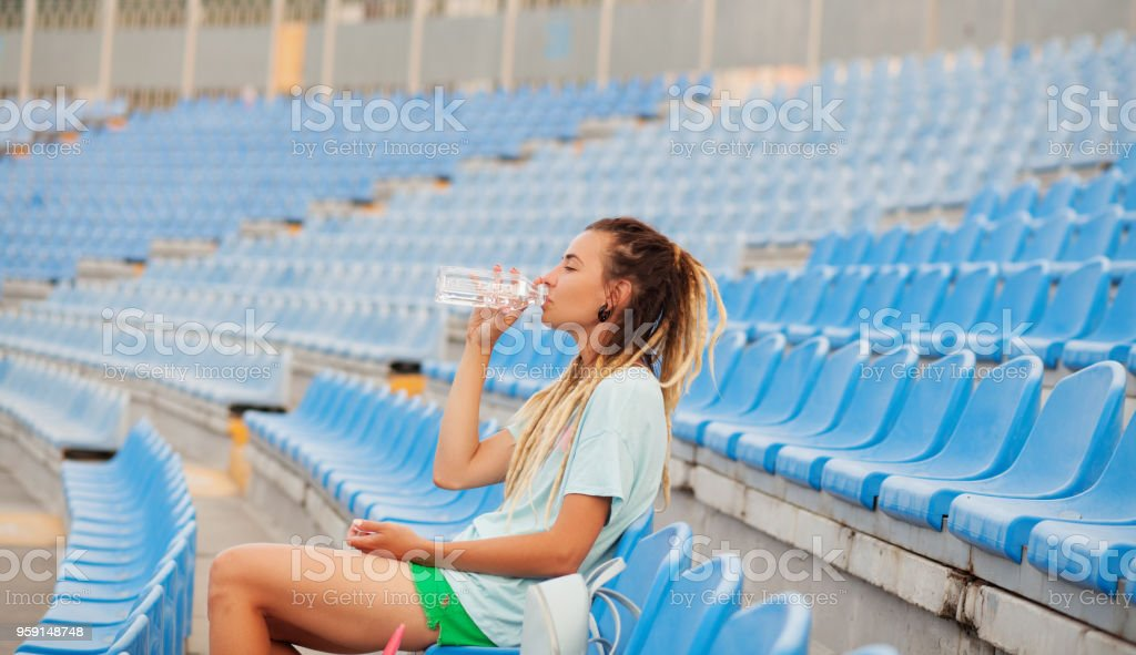 Street style portrait of beautiful stylish woman drinking a water stock photo