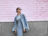 istock Street Style Shoot Woman on Pink Wall. Swag Girl Wearing Jeans Jacket, grey Dress, Sunglass. Fashion Lifestyle Outdoor 1284839442