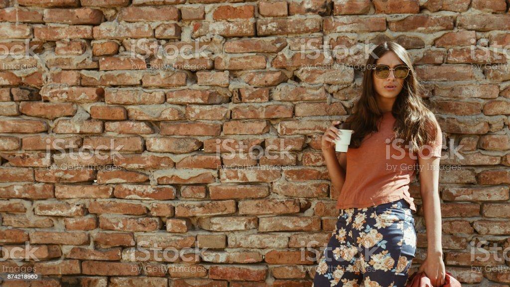 Street styled woman enjoying coffee stock photo