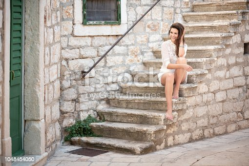 Beautiful natural model with a perfect candid smile sitting on stairs of an old town.   (NOTE: 1 week release!)