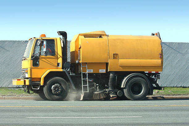 Street Sweeper Road sweeper moving slowly as it sweeps and vacuums up road debris on a city street. Side view, early morning. street sweeper stock pictures, royalty-free photos & images