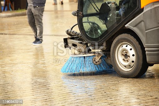 A street sweeper sweeps up a stone pavement with a strong brush in rainy weather. Maintaining clean tourist city. Preventing environmental disaster. Budget item of the city. Automation of the janitor.