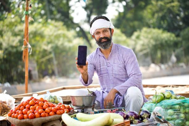 Street vegetable seller showing mobile phone stock photo