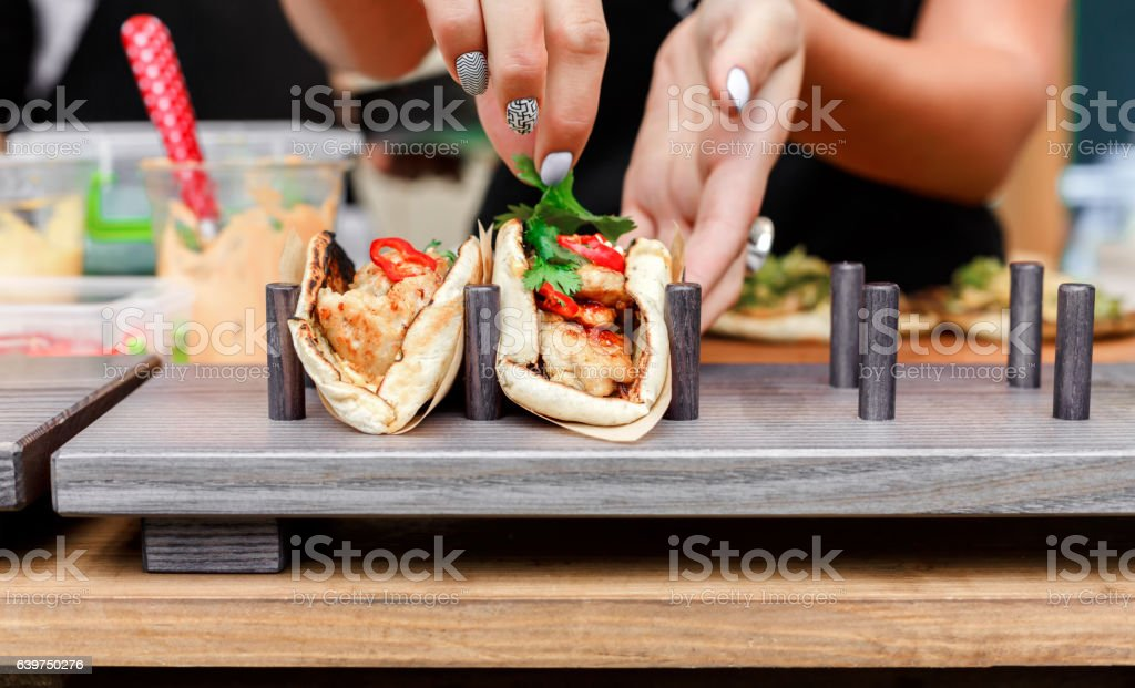 Street vendor hands making taco outdoors stock photo