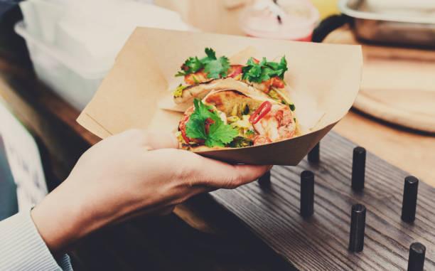 straßenverkäufer hände machen taco im freien - streetfood stock-fotos und bilder