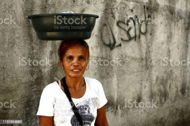 Street vendor peddling snack items balances the container with her picture id1152854865?b=1&k=6&m=1152854865&s=612x612&h=tp8h7zyitprhzya2yzpriegou59k2ayqxwucwjfddws=