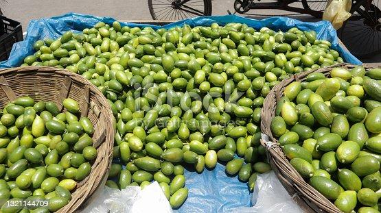 istock Street vendor selling lots of fresh green lemon on his van and basket at street of Dhaka, Bangladesh 1321144709