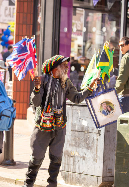 street vendor selling royal wedding clothing to the crowds of people on the streets of windsor leading towards windsor castle where the marriage of meghan markle and prince harry - matrimonio reale foto e immagini stock