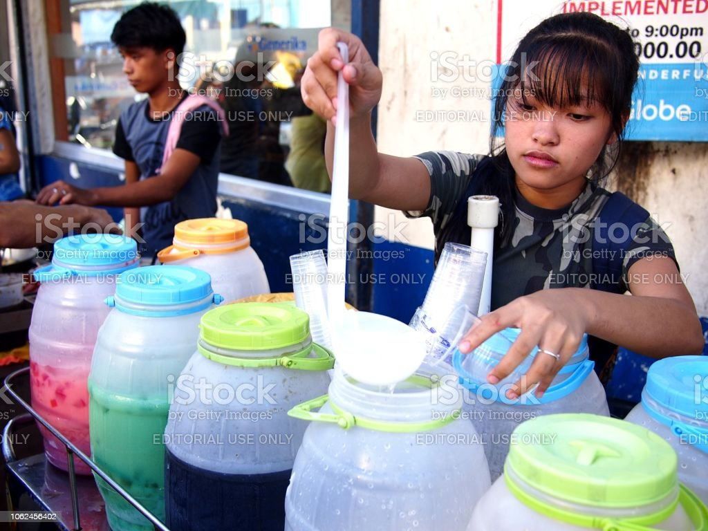 A street vendor sells assorted fruit juice and other refreshing drinks on her food cart at a sidewalk. stock photo