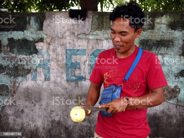 Street vendor slices a ripe pineapple which he sells on a sidewalk picture id1062467740?b=1&k=6&m=1062467740&s=612x612&h=6jyxzigiwqx2k2uadukogoj63 wixjsauccgxkav m0=