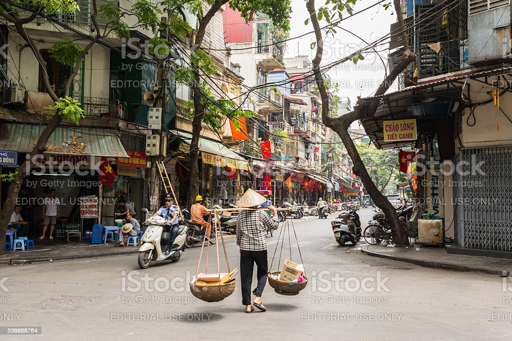 Street vendor transporting goods in baskets in Hanoi stock photo