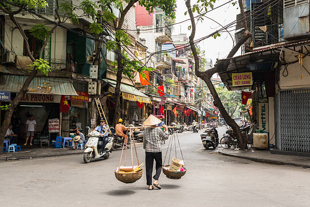 Street vendor transporting goods in baskets in Hanoi Hanoi, Vietnam - May 19, 2016: Street vendor carrying transporting goods in baskets using a carrying pole, also called a shoulder pole, in Hanoi's Old Quarter. hanoi stock pictures, royalty-free photos & images