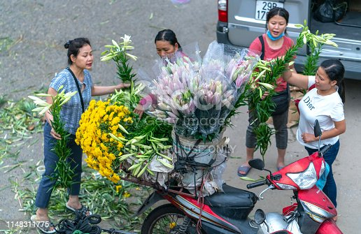 Hanoi, Vietnam - April 1st, 2019: A street vendor vendors are fresh lily flowers from the back of her bike in the historic old quarter of Hanoi, Vietnam
