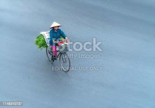 Hanoi, Vietnam - April 1st, 2019: Street vendors are hurriedly cycling across the street to find customers in the small neighborhood in Hanoi, Vietnam