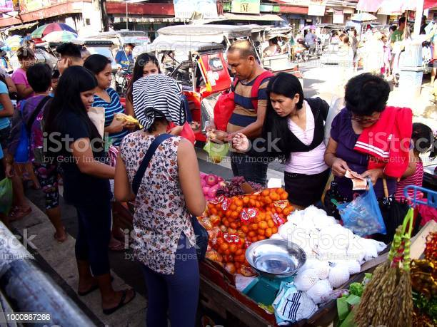Street vendors sell assorted fresh fruits and vegetables along a busy picture id1000867266?b=1&k=6&m=1000867266&s=612x612&h=nmibmh2ha0zh2ggrh0sgh09e2knewsw s7fnyy5fsmg=