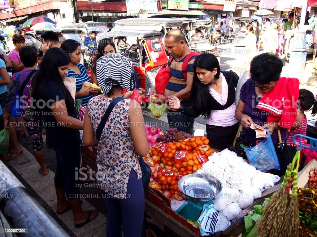 Street vendors sell assorted fresh fruits and vegetables along a busy street. stock photo
