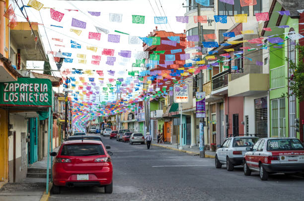 Street view. Alto Lucero, Veracruz, Mexico Alto Lucero, Veracruz, Mexico- January 1, 2018: Street view with colorful cut paper, cars, stores and houses at twilight in Alto Lucero, Mexico veracruz stock pictures, royalty-free photos & images