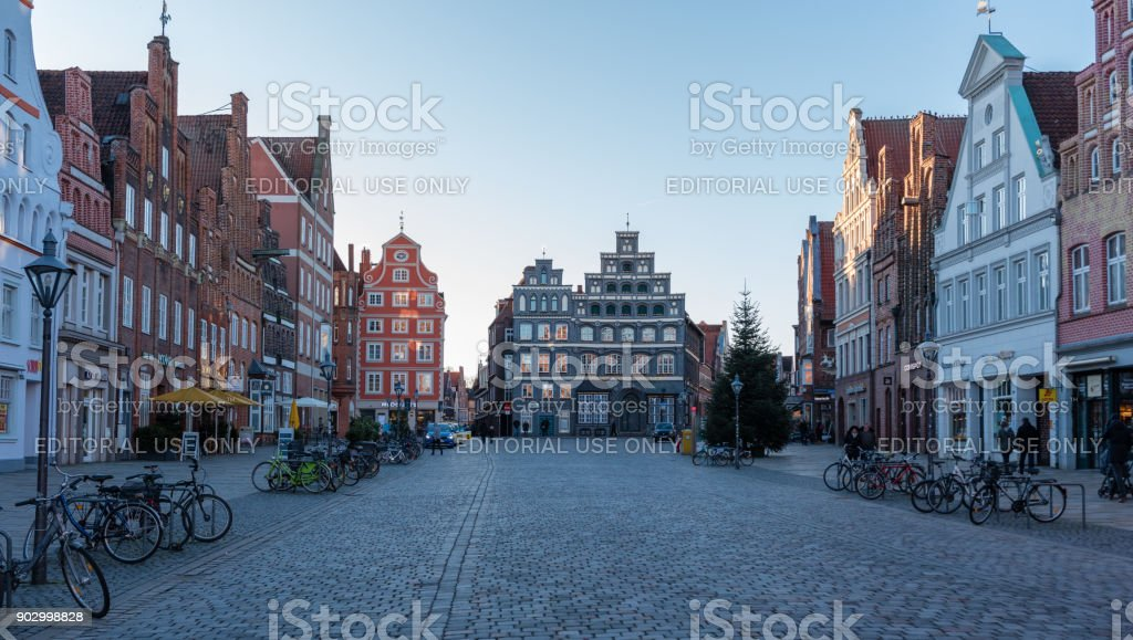 street view in Luneburg Germany - Am Sande region Photo is taken on a street in Am Sande region of Lüneburg, Germany. Lüneburg is written as 'Lunenburg' in English. Unique architecture of houses is seen in the photo. Street is surrounded by houses and there also bicycles parked in front of the houses. Photo is taken on a clod winter day in January 2018. Architecture Stock Photo