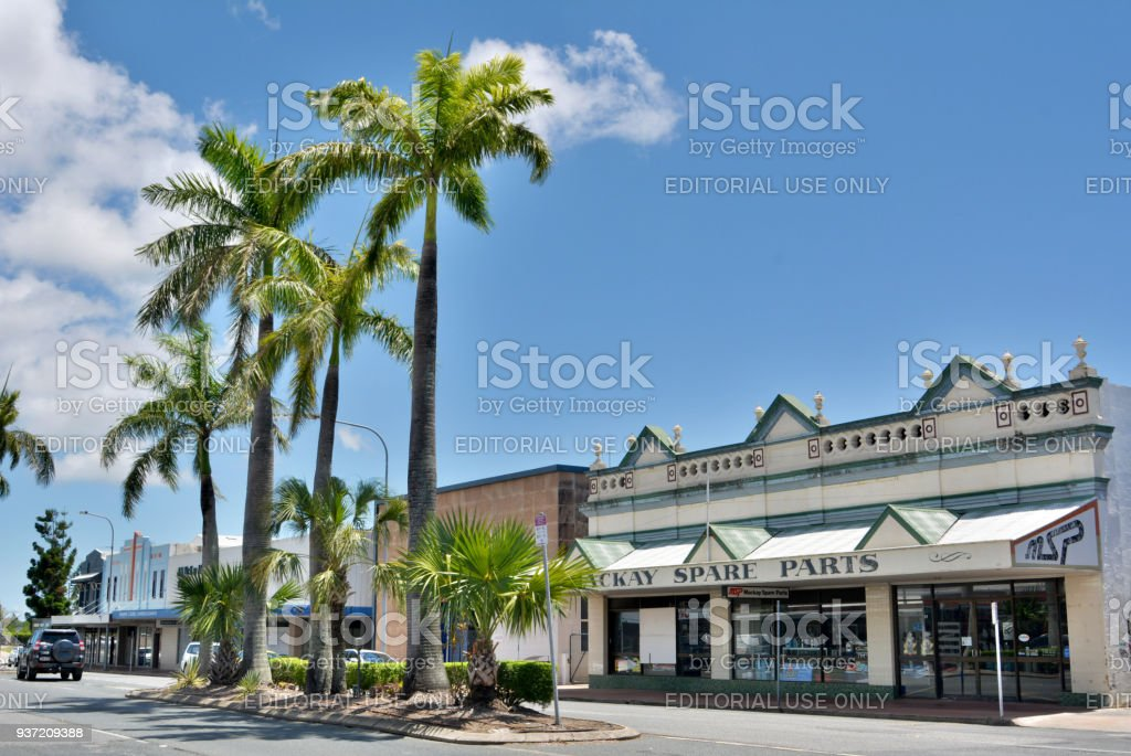 Street view in Mackay, QLD Mackay, Queensland, Australia - December 28, 2017. Street view in Mackay, QLD, with historic art deco buildings, commercial properties, car and palm trees. Aging Process Stock Photo