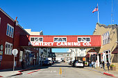 Monterey, California, United States of America - November 29, 2017. Street view in the Cannery Row district of Monterey, with historic buildings, wooden skywalk, cars and people.
