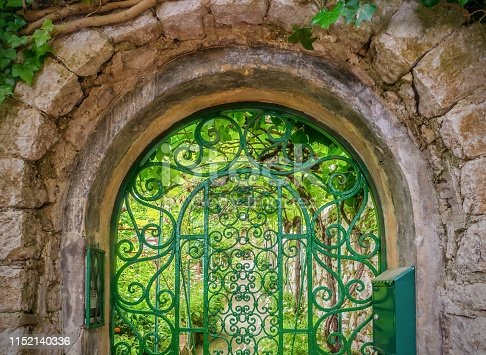 The old stone entryway is rounded on top, and covered with climbing vines. The arched, wrought iron gate is painted green and has an ornate, decorative, ornamental design. Inside the gate are a vine-covered wall, a path, and a secret garden of green plants lit by beautiful light.