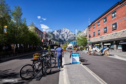 Banff, Alberta, Canada - August 9, 2020: Street view of famous Banff Avenue on a sunny afternoon during Covid-19 Pandemic.Tourists walking and warning sign in the middle of the street.