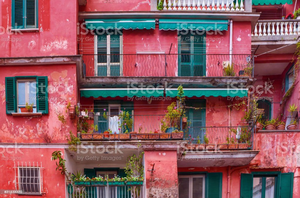 Street view of brightly colored, artistically painted old apartment building with peeling pink paint. Amalfi Coast, Italy. stock photo