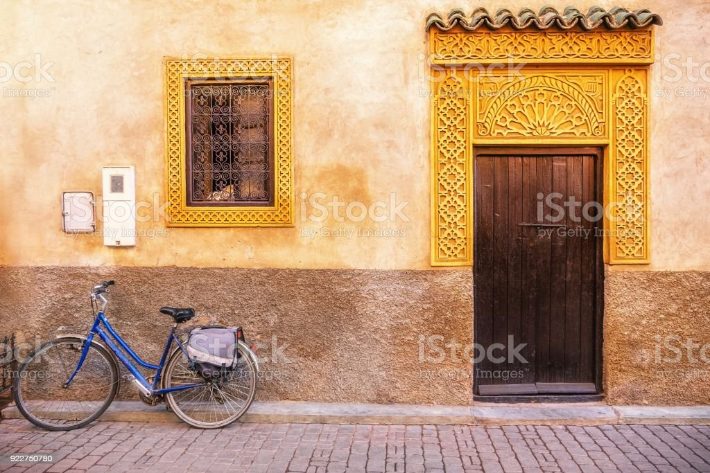 Street view of house exterior with ornate gold colored window and door frames, in Morocco stock photo