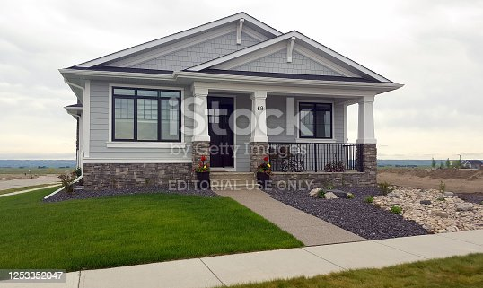 Calgary,Alberta, Canada- June 24,2020:  Front view of new bungalow on a corner lot. New housing development. Landscaped with lawn and dry river bed rock.