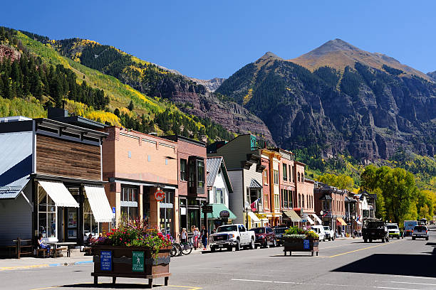 Street View of Telluride in Colorado Telluride, USA - September 24, 2015. Street view from Colorado Avenue with people walking on sidewalk in historic Telluride, Colorado. Telluride is a resort town surrounded by steep peaks of San Juan Mountains in the San Miguel County of southwestern Colorado. It is a very popular tourist destination year-round. People are allured to this town by its mountain scenery, art galleries, restaurants and top ranked ski facilities. san juan mountains stock pictures, royalty-free photos & images